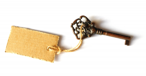 An old-fashioned brass key with cardboard label tied to it with twine